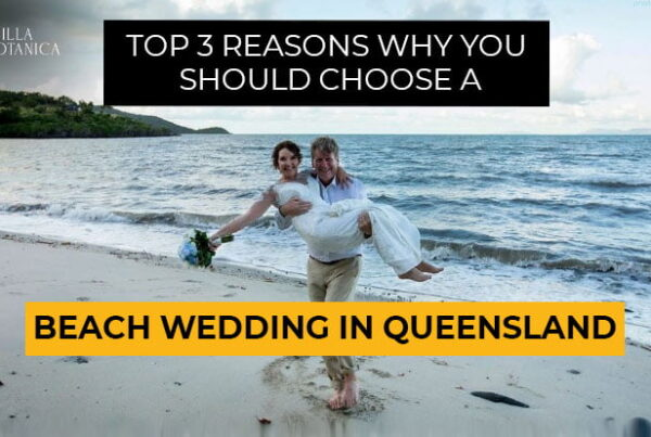 """groom carrying his bride on his arms at the Villa Botanica Whitsunday Wedding Venue beach with a banner text """"Top 3 Reasons Why You Should Choose a Beach Wedding Queensland"""""""