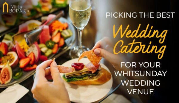 "banner image of a person holding a food on a table filled with foods and champagne with a title of ""Picking The Best Wedding Catering For Your Whitsunday Wedding Venue"""